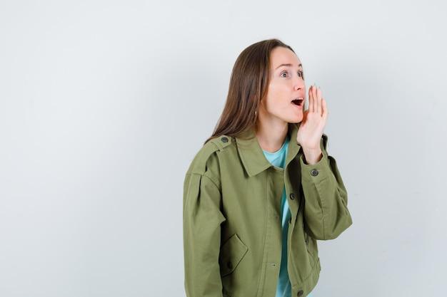 Jonge dame in t-shirt, jas die iets met de hand schreeuwt en er serieus uitziet, vooraanzicht.