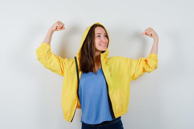 Jonge dame in t-shirt, jas die winnaargebaar toont en er gelukkig uitziet, vooraanzicht.