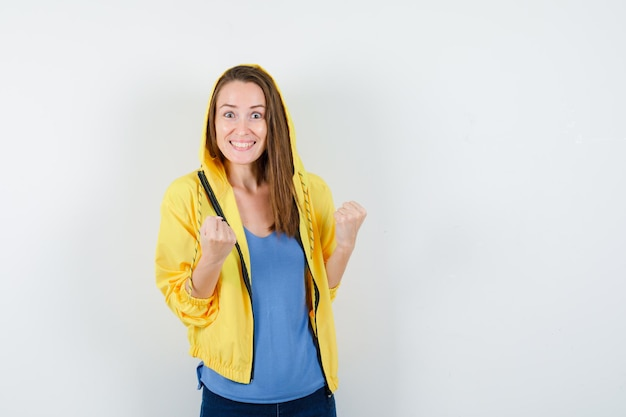 Jonge dame in t-shirt, jas die winnaargebaar toont en er gelukzalig uitziet