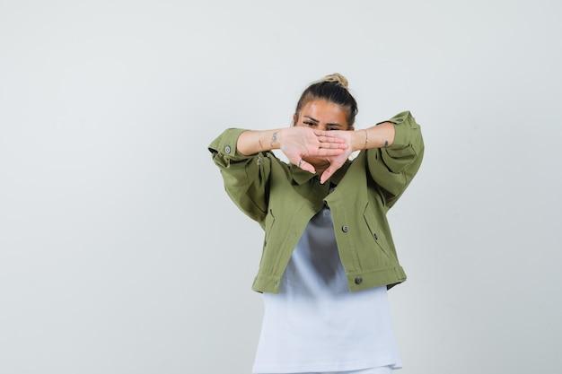 Jonge dame in t-shirt jas gezicht achter handen verbergen en beschaamd kijken