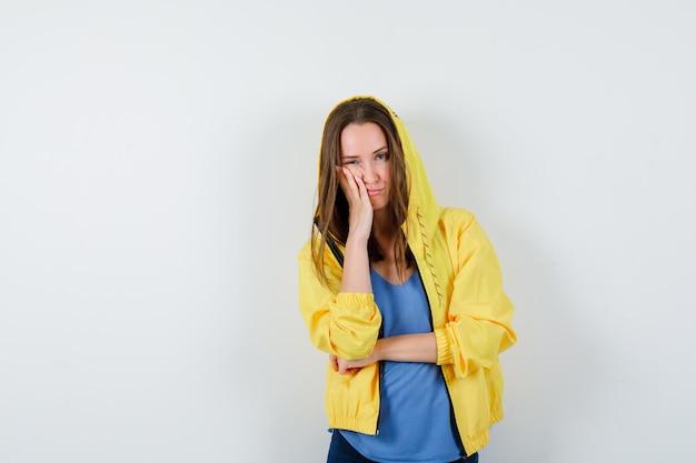 Jonge dame in t-shirt, jas houdt hand op wang en kijkt verdrietig