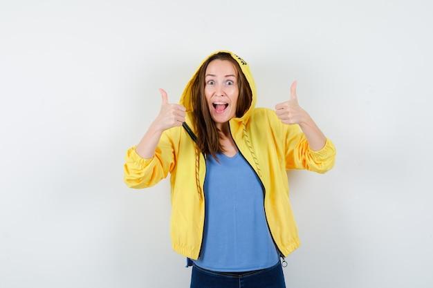 Jonge dame in t-shirt, jas met dubbele duimen omhoog en ziet er gelukkig uit, vooraanzicht.