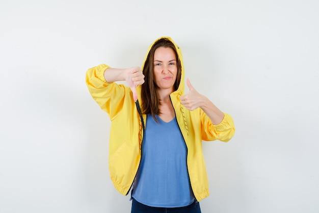 Jonge dame in t-shirt, jas met duimen op en neer en zelfverzekerd, vooraanzicht.
