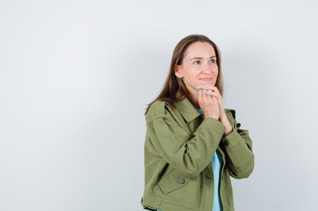 Jonge dame in t-shirt, jas met gevouwen handen op kin en ziet er mooi uit, vooraanzicht.