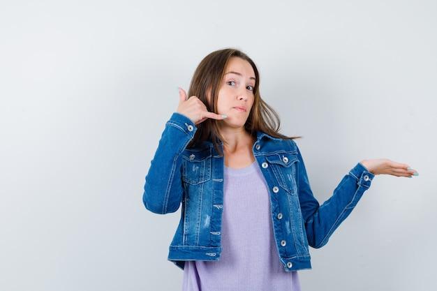 Jonge dame in t-shirt, jas met telefoongebaar, palm opzij spreidend en zelfverzekerd, vooraanzicht.