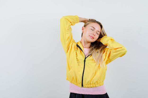 Jonge dame in t-shirt, jas poseren tijdens het regelen van haar horen en er aantrekkelijk uitzien
