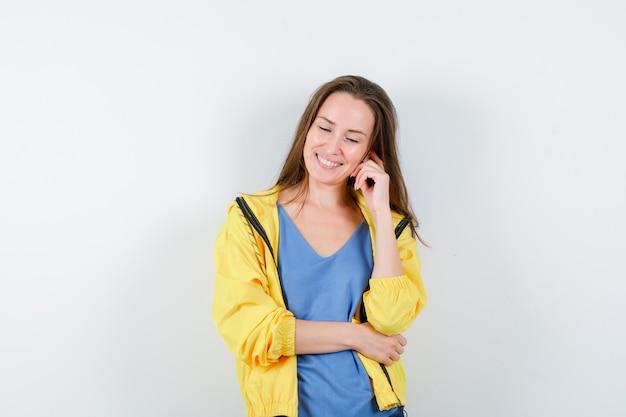 Jonge dame in t-shirt, jas staat in denkende houding en ziet er optimistisch uit, vooraanzicht.