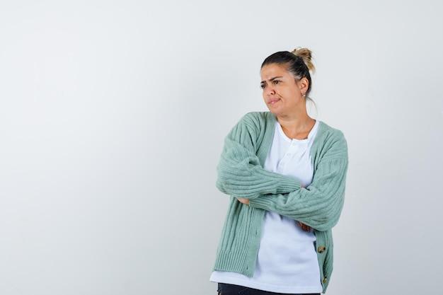 Jonge dame in t-shirt, jas staat met gekruiste armen en kijkt bedachtzaam