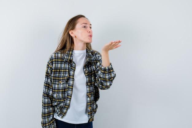 Jonge dame in t-shirt, jas waait luchtkus met pruilende lippen en ziet er schattig uit, vooraanzicht.