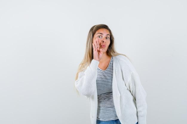 Jonge dame in t-shirt, jasje dat geheim met hand dichtbij mond vertelt en nieuwsgierig, vooraanzicht kijkt.