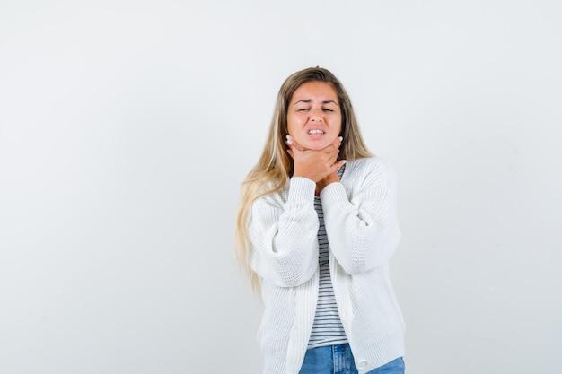 Jonge dame in t-shirt, jasje die aan keelpijn lijdt en ziek kijkt, vooraanzicht.