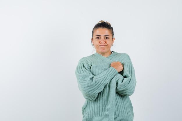 Jonge dame in t-shirt, jasje inpakkend en weemoedig kijkend