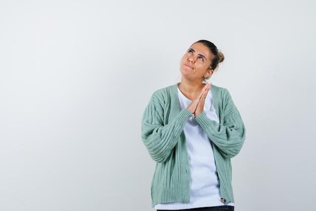 Jonge dame in t-shirt, jasje met biddend gebaar en hoopvol kijkend