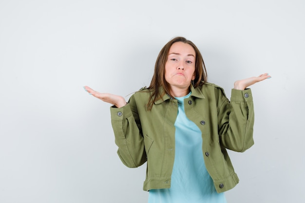 Jonge dame in t-shirt, jasje met hulpeloos gebaar en op zoek clueless, vooraanzicht.