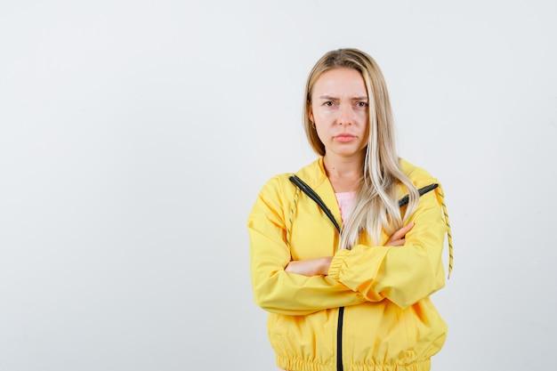Jonge dame in t-shirt, jasje permanent met gekruiste armen en op zoek zelfverzekerd