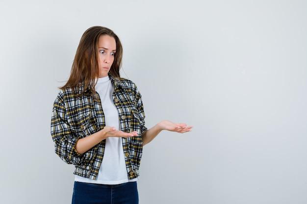 Jonge dame in t-shirt, jasje, spijkerbroek die doet alsof ze iets laat zien en er verbaasd uitziet, vooraanzicht.
