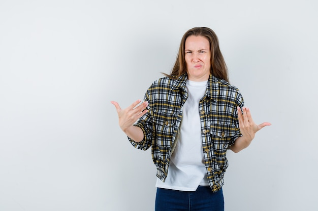 Jonge dame in t-shirt, jasje, spijkerbroek die hulpeloos gebaar toont terwijl ze lippen buigt en aarzelend kijkt, vooraanzicht.