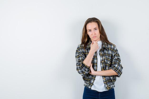 Jonge dame in t-shirt, jasje, spijkerbroek die zich in het denken stelt stelt en peinzend kijkt, vooraanzicht.