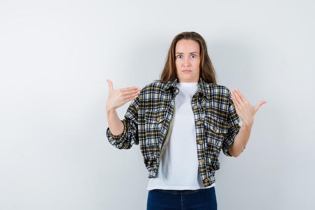 Jonge dame in t-shirt, jasje, spijkerbroek die zichzelf met handen richt en verbaasd kijkt, vooraanzicht.