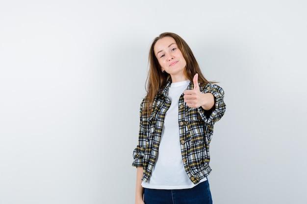 Jonge dame in t-shirt, jasje, spijkerbroek met duim omhoog en op zoek naar zelfverzekerd, vooraanzicht.