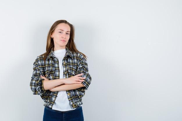 Jonge dame in t-shirt, jasje, spijkerbroek permanent met gekruiste armen en op zoek naar zelfverzekerd, vooraanzicht.