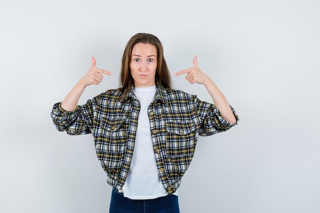 Jonge dame in t-shirt, jasje, spijkerbroek wijzend naar zichzelf en op zoek trots, vooraanzicht.