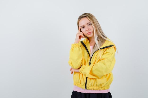 Jonge dame in t-shirt, jasje staande in denken pose en peinzend kijken