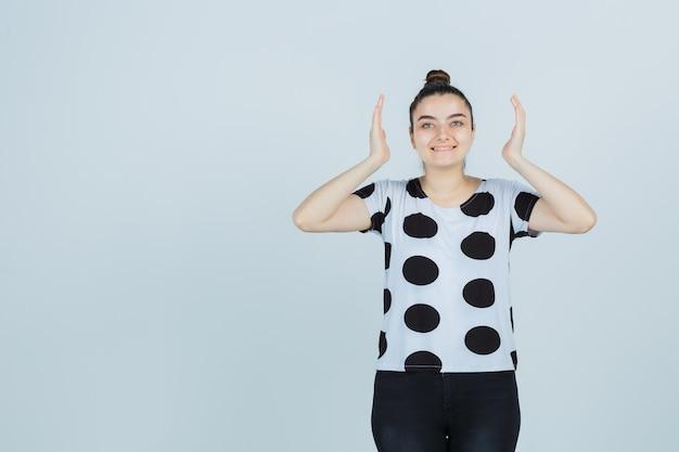 Jonge dame in t-shirt, jeans die grootteteken toont en gelukkig, vooraanzicht kijkt.