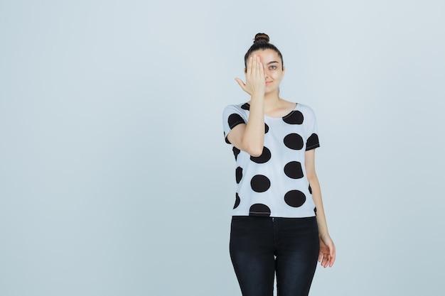 Jonge dame in t-shirt, jeans die hand op oog houdt en zelfverzekerd kijkt, vooraanzicht.