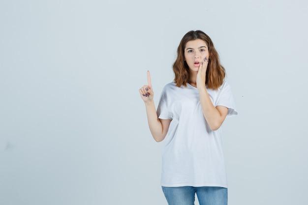 Jonge dame in t-shirt, jeans die omhoog wijst terwijl hand op wang wordt gehouden en verbaasd, vooraanzicht kijkt.