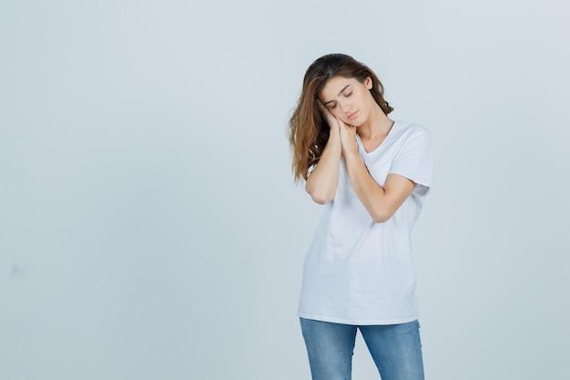 Jonge dame in t-shirt, jeans die op handen als hoofdkussen leunt en slaperig, vooraanzicht kijkt.