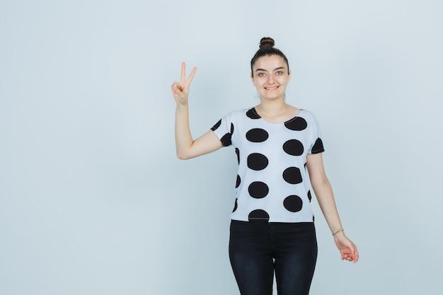 Jonge dame in t-shirt, jeans die overwinningsteken toont en gelukkig, vooraanzicht kijkt.