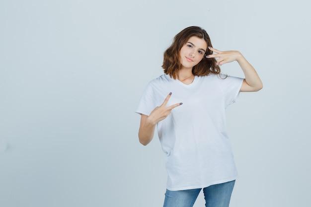 Jonge dame in t-shirt, jeans die overwinningsteken toont en vrolijk, vooraanzicht kijkt.