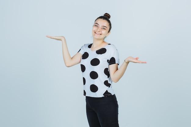 Jonge dame in t-shirt, jeans die schalengebaar toont en gelukkig, vooraanzicht kijkt.