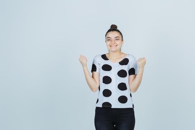Jonge dame in t-shirt, jeans die winnaargebaar toont en gelukkig, vooraanzicht kijkt.