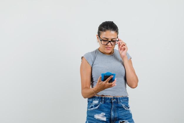 Jonge dame in t-shirt, korte broek kijkt uit over notities op mini klembord