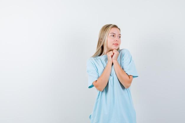 Jonge dame in t-shirt met gevouwen handen in smekend gebaar en hoopvol kijkend
