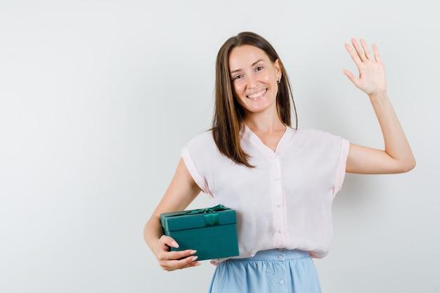 Jonge dame in t-shirt, rok die huidige doos houdt terwijl palm toont en vreugdevol, vooraanzicht kijkt.