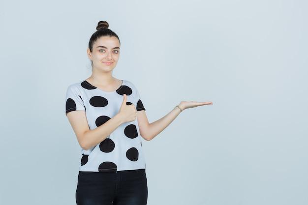 Jonge dame in t-shirt, spijkerbroek die doet alsof ze iets laat zien terwijl ze de duim laat zien en er zelfverzekerd uitziet, vooraanzicht.