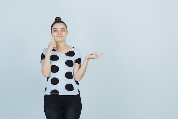Jonge dame in t-shirt, spijkerbroek die vinger op de wang drukt terwijl ze naar de rechterkant wijst en er zelfverzekerd uitziet, vooraanzicht.