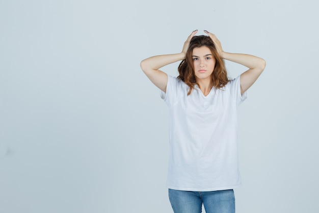 Jonge dame in t-shirt, spijkerbroek hand in hand op het hoofd en op zoek moe, vooraanzicht.