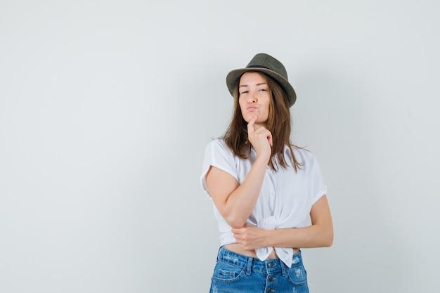 Jonge dame in t-shirt, spijkerbroek, hoed staande in denken pose en op zoek verstandig, vooraanzicht.
