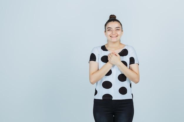 Jonge dame in t-shirt, spijkerbroek met gevouwen handen op de borst en op zoek naar hoopvol, vooraanzicht.