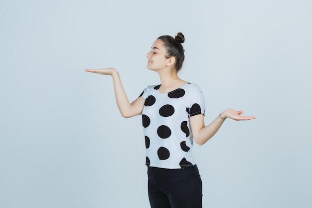 Jonge dame in t-shirt, spijkerbroek met schalen gebaar terwijl wegkijken en op zoek gelukkig, vooraanzicht.