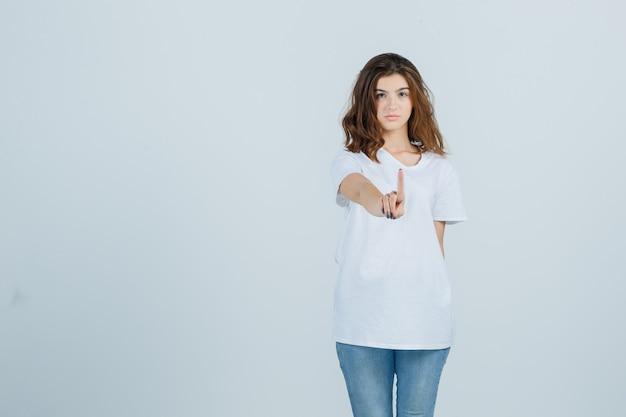 Jonge dame in t-shirt, spijkerbroek wacht even en ziet er zelfverzekerd uit, vooraanzicht.