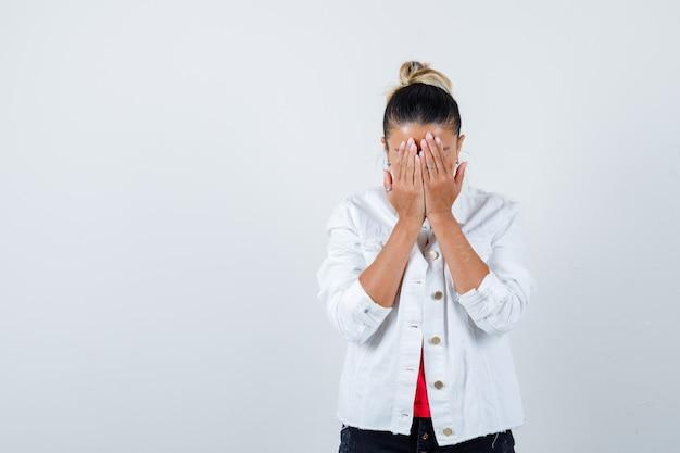 Jonge dame in t-shirt, witte jas die het gezicht bedekt met handen en er teleurgesteld uitziet, vooraanzicht.