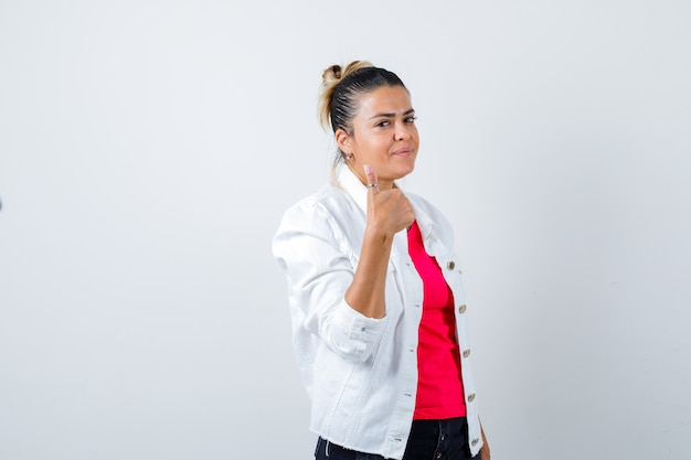 Jonge dame in t-shirt, witte jas met duim omhoog en ziet er tevreden uit, vooraanzicht.