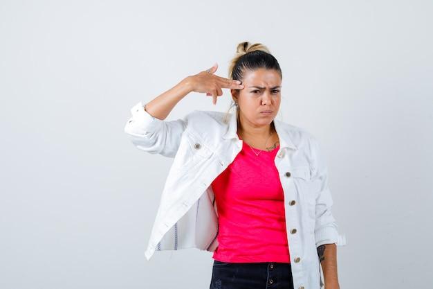 Jonge dame in t-shirt, witte jas met geweergebaar en verveeld, vooraanzicht.