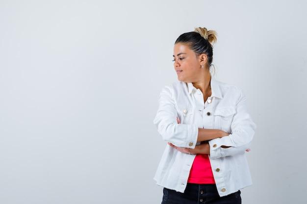 Jonge dame in t-shirt, witte jas staat met gekruiste armen en ziet er zelfverzekerd uit, vooraanzicht.