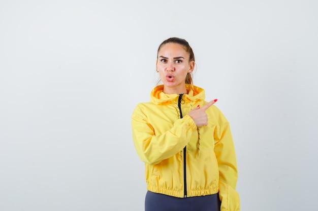 Jonge dame in trainingspak die naar de rechterbovenhoek wijst en zich afvraagt, vooraanzicht.